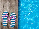 Flip flop sandals on old wooden boards near swimming pool — Stock Photo