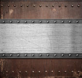 Old metal plate over rusty background with rivets — Stock Photo
