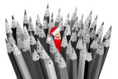 Pencil with smile in Santa's Christmas hat among sad gray pencil — Stock Photo