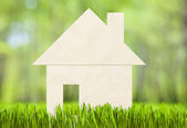 Paper house on green grass concept — Stock Photo