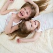 Happy little girls lying on back top view — Stock Photo #38321375