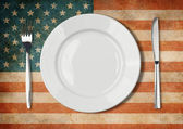 Plate, fork and kinife one grunge USA flag — Stock Photo