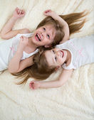 Happy little girls lying on back top view — Stock Photo