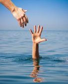 Helping hand giving to drowning man in sea — Stock Photo