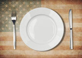 Plate, fork and knife on old USA flag — Stock Photo
