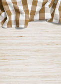 Folded tablecloth over bleached wooden table — Stock Photo