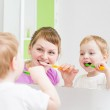 Happy mother and child teeth brushing in bathroom front of mirror — Stock Photo #40229703