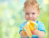Happy kid eating banana fruit. healthy food eating concept. — Stock fotografie