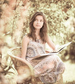 Girl reading book sitting outdoor in summer day. Retro stylized  — Stock Photo