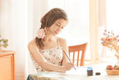 Girl writing at table by pen and ink at window. Retro stylized i — Stock Photo