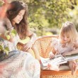 Girls reading book outdoor in summer day. Retro stylized. — Stock Photo