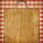 Hardboard or breadboard over red checked gingham picnic tableclot — Stock Photo