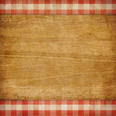 Cutting board over red grunge checked gingham picnic tablecloth — Stock Photo