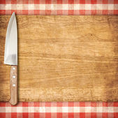 Cutting breadboard and knife over red grunge gingham tablecloth  — Stock Photo