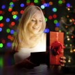 Young woman opening  gift box in front of christmas tree — Stock Photo #42268049