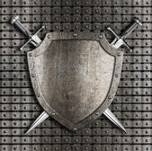 Shield and two swords crossed hanging on metal wall with rivets — Stock Photo