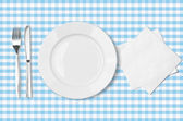 Plate, fork, knife and napkin over blue checked fabric tableclot — Stock Photo