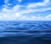 Sea or ocean water surface with blue sky and clouds — Stock Photo