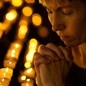 Gebed bidden in de katholieke kerk in de buurt van kaarsen. religie concept — Stockfoto