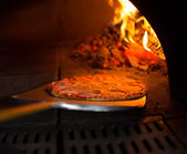Ready pizza getting from oven — Stok fotoğraf