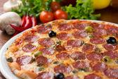 Italian salami pizza on table with vegetables — Stok fotoğraf