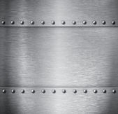 Brushed metal background with rivets — Stock Photo