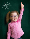 Happy kid girl in glasses with bright idea standing near school — Stock Photo