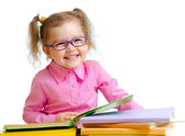 Happy child girl in glasses reading books sitting at table  — Stock Photo