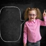 Funny child in eyeglasses standing near school chalkboard  as a  — Stockfoto #46783743