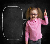 Funny child in eyeglasses standing near school chalkboard  as a  — Stock Photo