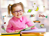 Happy child girl in glasses reading books in library — Stock Photo