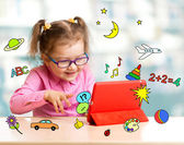 Child sitting with tablet computer and learning or playing with  — Stock Photo