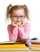 Child girl in glasses reading book and smiling — 图库照片