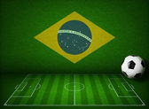 Soccer or football field with ball and flag of Brazil — Stock Photo