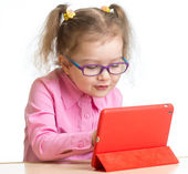 Kid in glasses looking at mini tablet pc screen sitting at table — Stock Photo