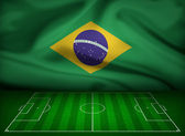 Soccer field with flag of Brazil background — Stock Photo