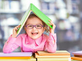 Little girl in glasses under roof made from book. — Stock Photo