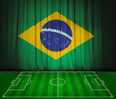 Soccer field with flag of Brazil on green curtain — Stock Photo