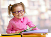 Happy child girl in eyeglasses reading books sitting at table  — Stock Photo