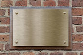 Brass or bronze metal plate on brick wall — Stock Photo