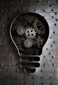 Concept idea: bulb with working gears and cogs — Stock Photo