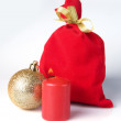 Red bag for gift with gold ribbon christmas balls and burning candle — Stock Photo #16187939