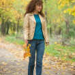 Beautifull girl walk in autumn park — Stock Photo #27529591