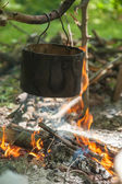 Pot for cooking on a fire in a campaign — Stock Photo