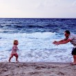 Stock Photo: Father and daughter playing together on the beach at sunset