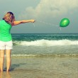 Beautiful girl with green balloon on the beach. Old style colour — Stock Photo #14918227
