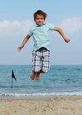 7 let chlapec skákání v moři — Stock fotografie