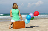Beautiful girl sitting on vintage suitcase on the beach — Stock Photo