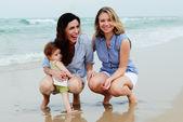Bebek plajda iki güzel kızla — Stok fotoğraf