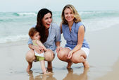 Two beautiful girls with a baby on the beach — Stok fotoğraf